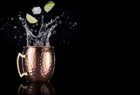 lime and ice falling into a splashing moscow mule cocktail isolated on black background 免版税图像