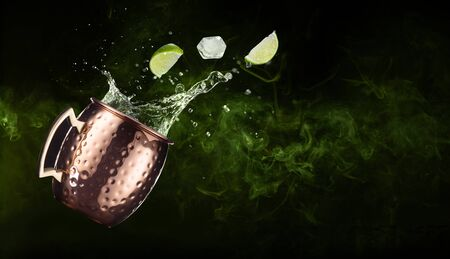 lime and ice falling out of a splashing moscow mule on smoky background