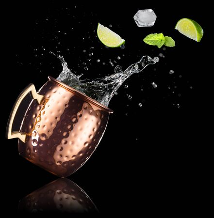 mint, lime and ice cube falling out of a splashing moscow mule isolated on black