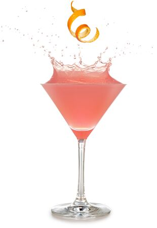 orange rind falling into a splashing pink cocktail isolated on white