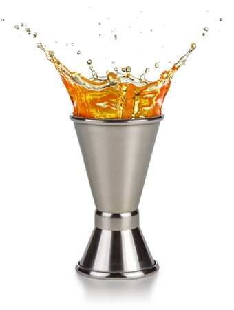 orange liquor spilling out of a jigger isolated on white background
