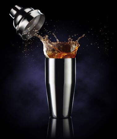 amber liquor spilling out of a shaker isolated on dark blue background