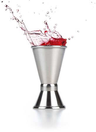 red liquid spilling out of a jigger isolated on white 免版税图像