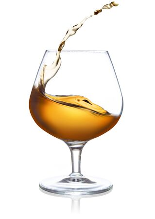 splash of cognac in a snifter isolated on white