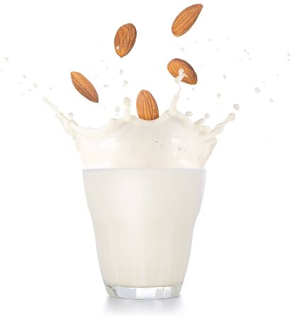 almonds falling into a splash of milk glass isolated on white background
