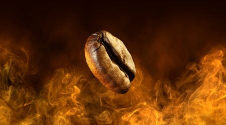 close up of coffee bean flying in a dark orange smoky background 免版税图像
