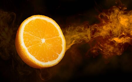 close up of a cut orange in a smoke swirl flying on dark background