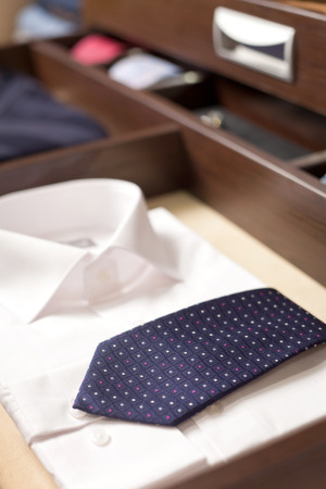 Folded men's white shirt with bkue tie in the wardrobe 스톡 콘텐츠