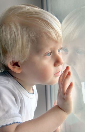 window  glass: Little boy looking out the window Stock Photo