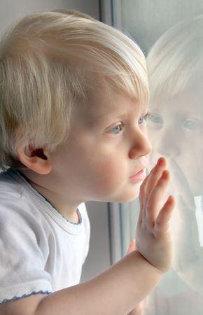 ojos tristes: Ni�o mirando por la ventana Foto de archivo