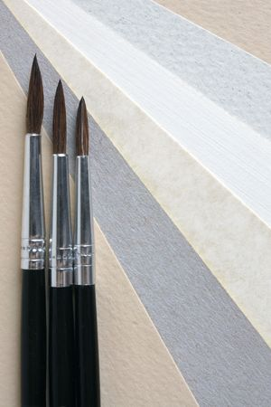 Paint brushes on papers background, a vertical picture Stock Photo - 6231817