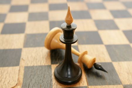 chessmen: Old chessmen on the crackled chessboard background