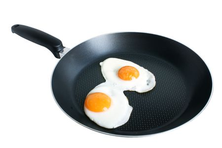Fried eggs on griddle isolated on the white backgroun photo