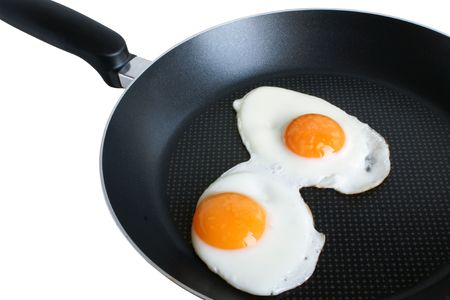 Fried eggs on griddle isolated on the white backgroun Stock Photo - 6363891