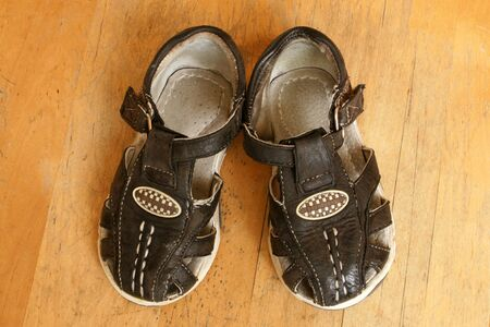 Childs sandals on a wooden background photo