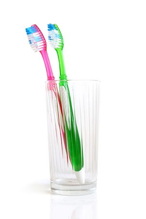 Two colorful tooth-brushes inside a glass, on a white background photo