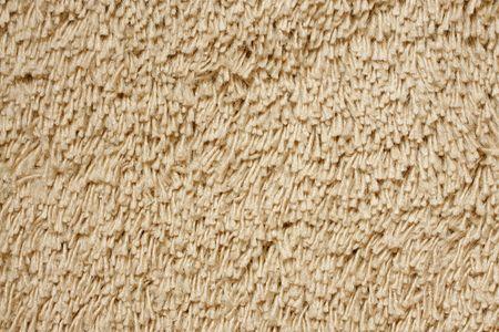 A beige carpet texture, close-up photo