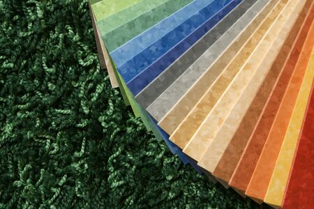 carpet and flooring: The samples of collection multicolored linoleum on green carpet background