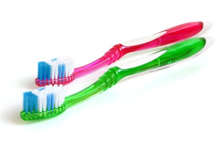 Two colorful tooth-brushes on a white background photo