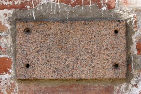 billboard blank: Old brick wall with a blank marble slab, for backgrounds or textures Stock Photo
