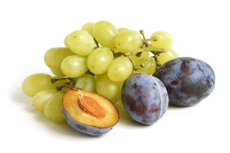 large group of objects: Bunch of grapes and plums on a white background