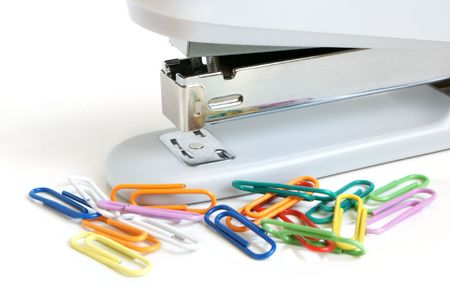 Stapler and multicolored paper clips on a white background photo
