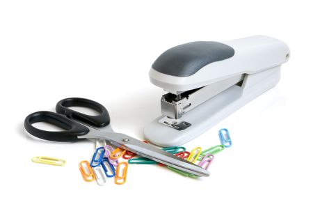 Scissors, stapler and multicolored paper clips on a white background photo