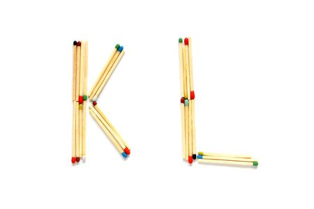 Letters K and L made of matches on a white background photo