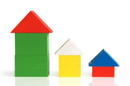 Houses made from childrens wooden building blocks on a white background photo