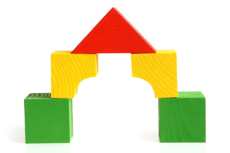 House made from childrens wooden building blocks on a white background photo