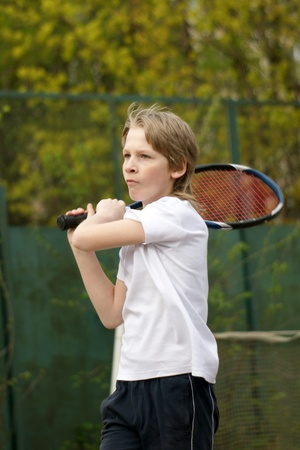 Boy playing tennis, a vertical picture photo