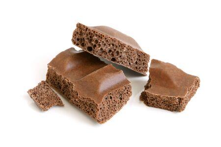 Porous chocolate pieces on a white background photo