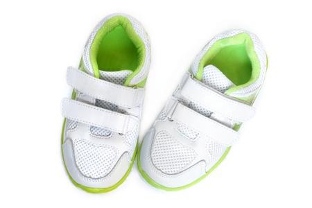 スニーカー: 白い背景の上の子供のスポーツの靴 写真素材