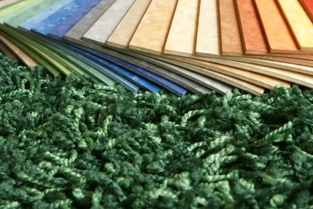 linoleum: The samples of collection multicolored linoleum on green carpet background