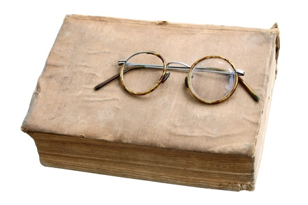 Old book with antique glasses isolated on a white background