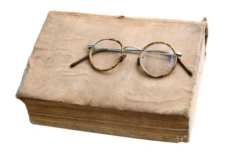 oud document: Oud boek met antieke bril geà ¯ soleerd op een witte achtergrond