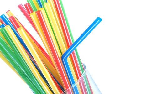 multi coloured: Cocktail straws in glass isolated on a white background
