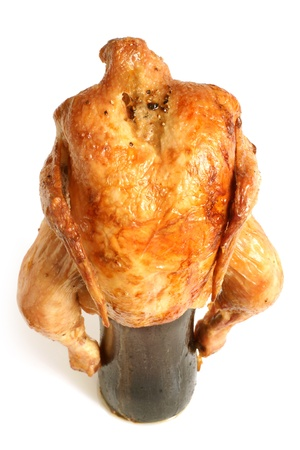 Marinated and roasted chicken on a beer bottle on a white background photo
