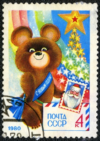 olympic symbol: USSR - CIRCA 1979: A stamp printed in USSR shows  Olympic Bear Holding Stamp - a symbol of the Moscow Olympics games, New Year 1980, circa 1979