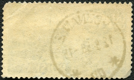 perforated stamp: The reverse side of a postage stamp on a black background