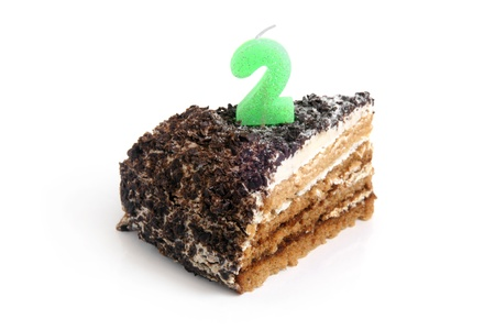 Slice of chocolate birthday cake with number two candle on a white background photo