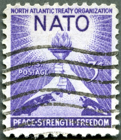UNITED STATES - CIRCA 1952: A stamp printed by USA shows Torch of Liberty and Globe, 3rd anniversary of the signing of the North Atlantic Treaty, circa 1952 Stock Photo - 12950245