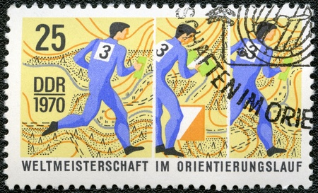 GERMANY- CIRCA 1970: A stamp printed by Germany, shows Competition map and runner at 3 different stations, World Orienting Championships, circa 1970 photo