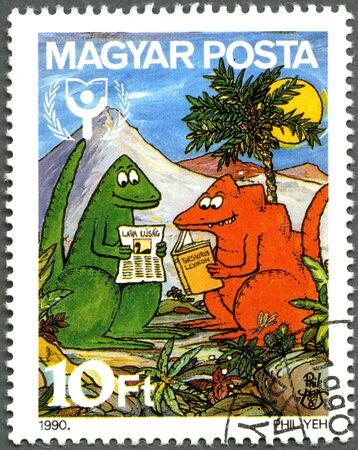 magyar: HUNGARY - CIRCA 1990: A stamp printed in Hungary shows Dinosaurs Reading Book, International Literacy Year, circa 1990