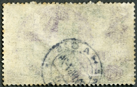 postcard back: The reverse side of a postage stamp on a black background
