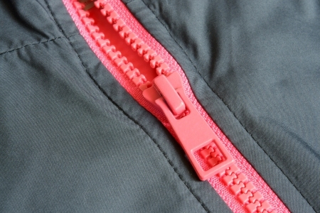 Closeup of pink zipper in gray cloth, a horizontal picture photo