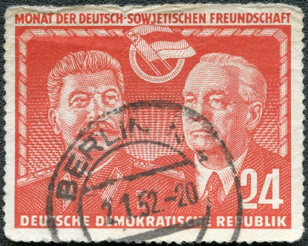 tyrant: GERMANY - CIRCA 1951: A stamp printed in Germany shows Stalin and Wilhelm Pieck, Month of East German-Soviet friendship, circa 1951 Stock Photo