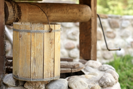 homestead: Detail of draw well with wooden bucket, a horizontal picture