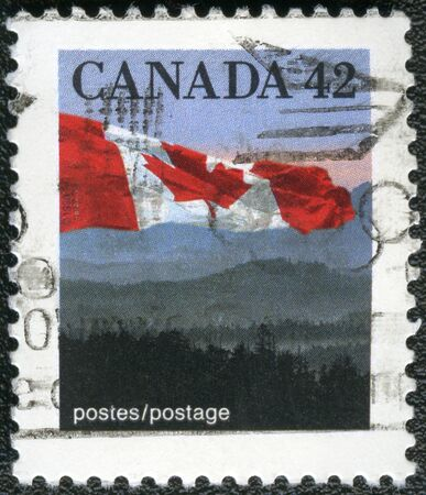 canada stamp: CANADA - CIRCA 1990: A stamp printed in Canada shows Canadian flag and Hills, circa 1990