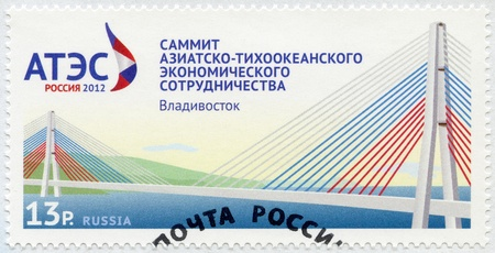 RUSSIA - CIRCA 2012: A stamp printed in Russia shows Official logo of the summit of APEC and the bridge on the Russky island, circa 2012 Stock Photo - 15670768